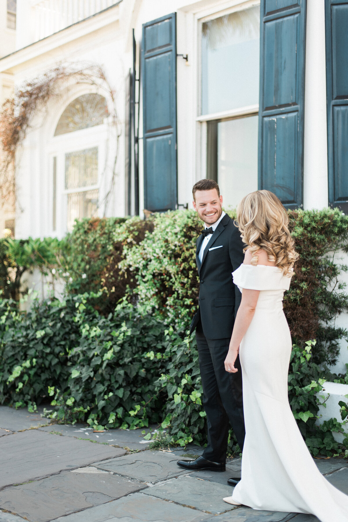Groom guides his bride along the side of an ivy covered building