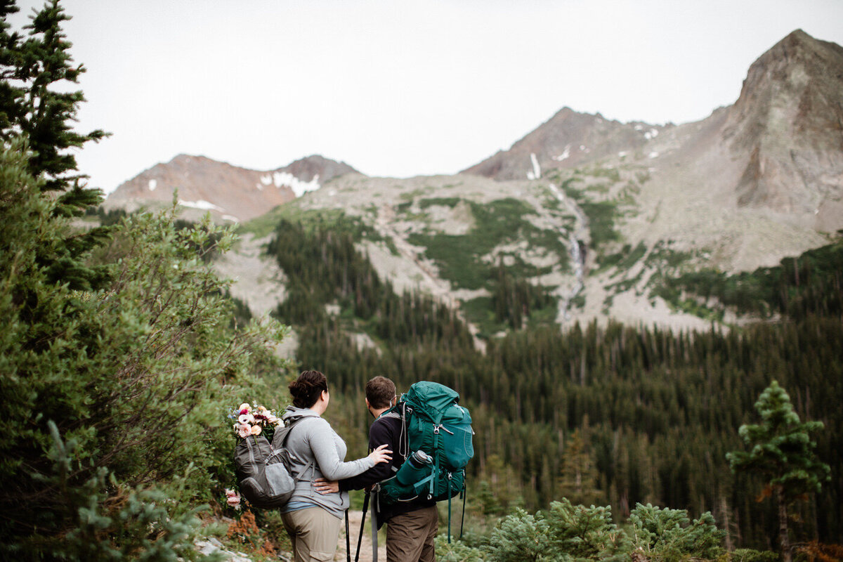 A couple holds each other while looking out over the mountains wearing hiking clothes and with a wedding bouquet strapped to the hiking backpack