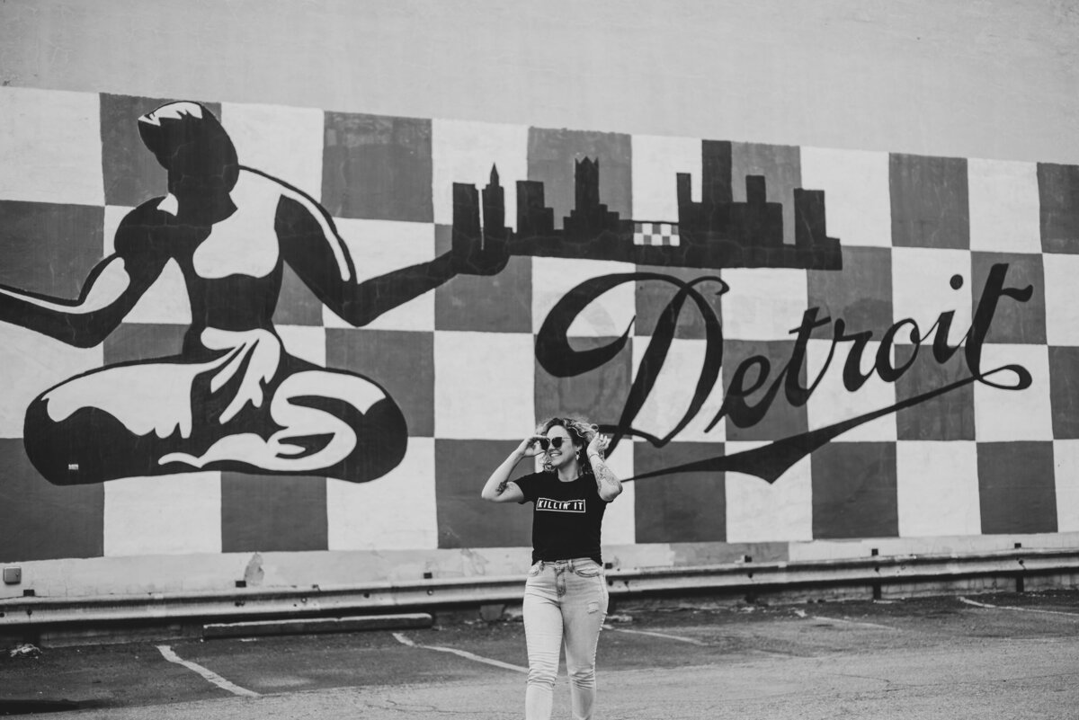 Woman in front of Iconic Detroit mural downtown.