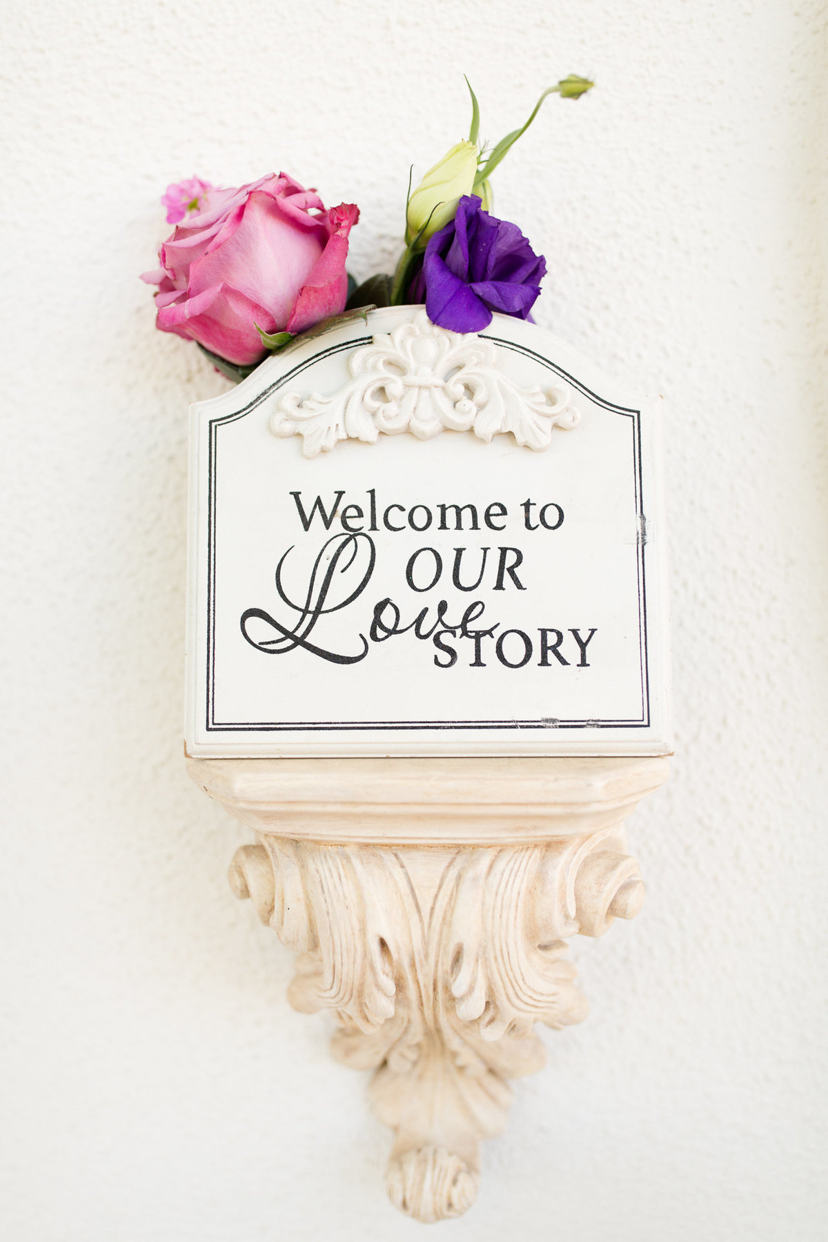 Welcome to our love story sign with pink and purple flowers at villa de amore by matty fran photography