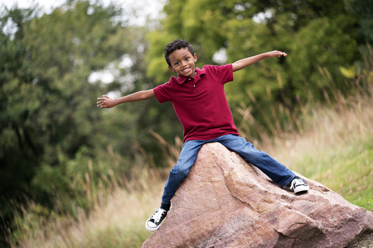 boy pretending to fly on rock at arboretum sioux falls