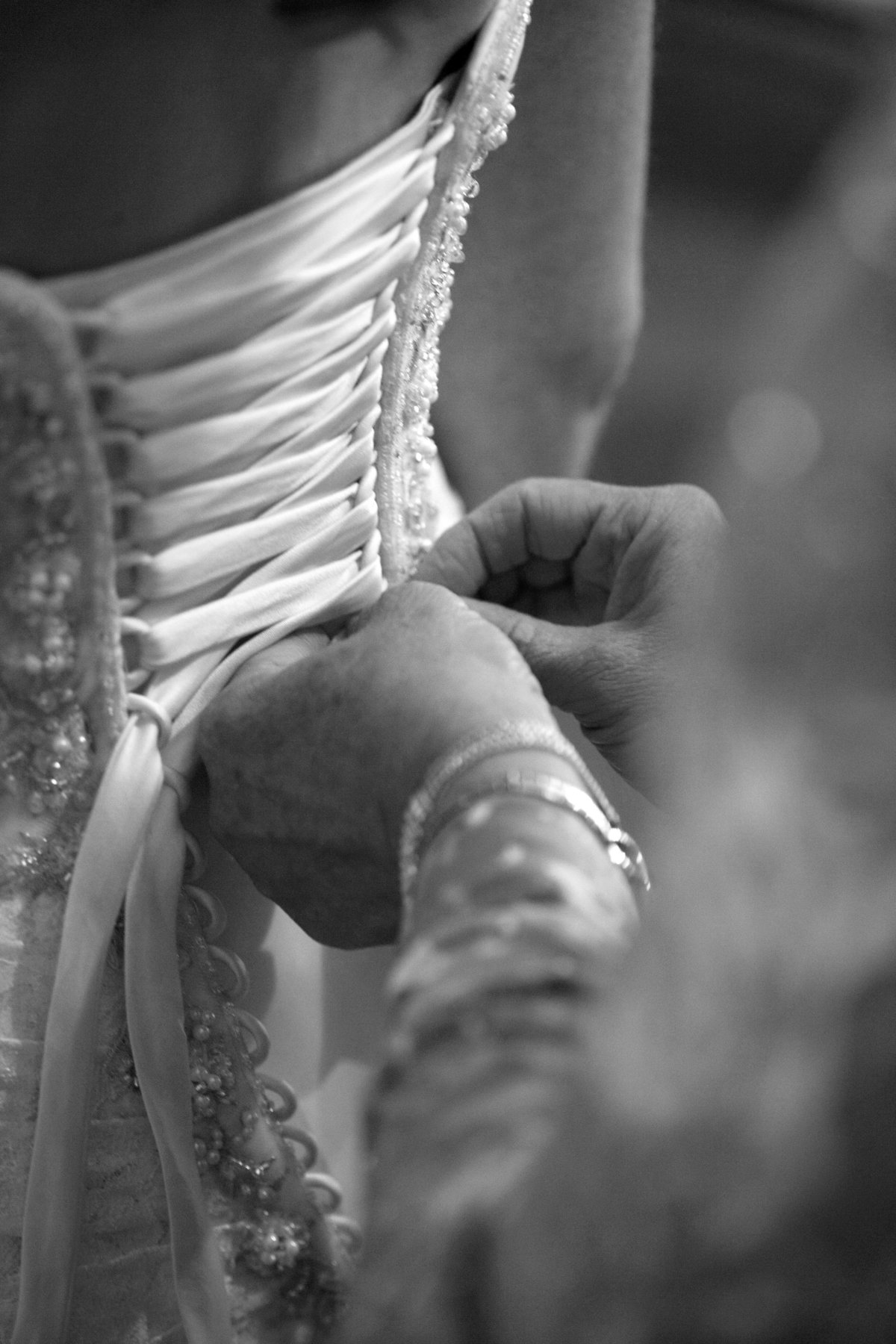 Black and white detail shot of mom lacing up bride's dress