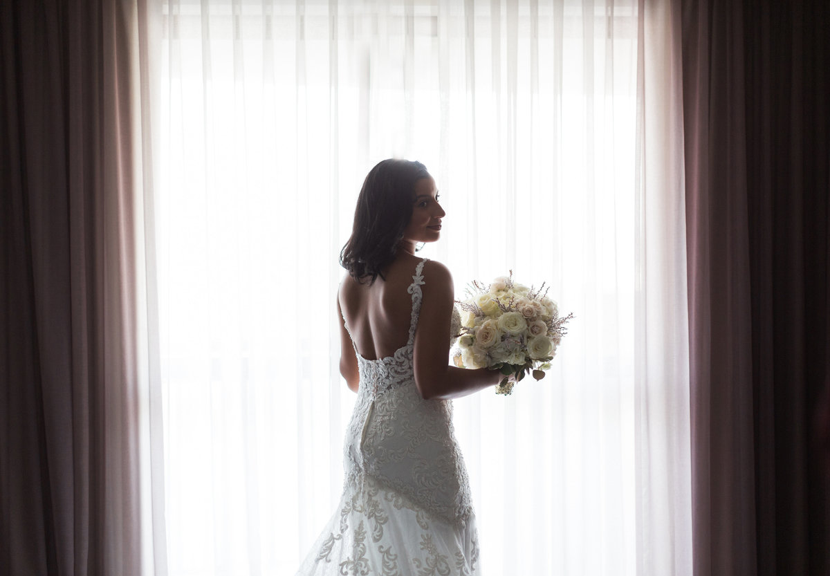 Bride standing in window at Renaissance hotel North Hill