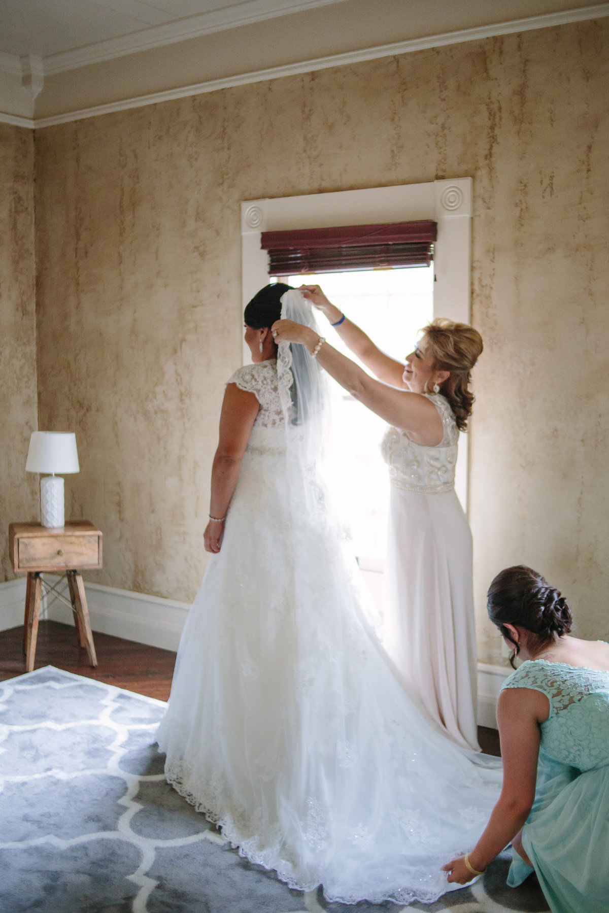 Mother of bride puts veil on her daughter just before getting ready for Texas Hill Country wedding ceremony.