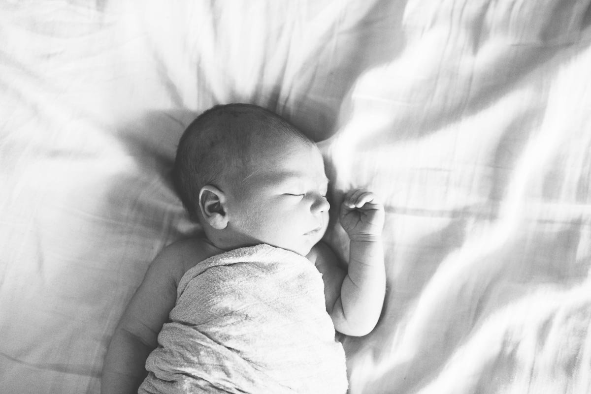 baby sleeping on white bed in black & white portrait