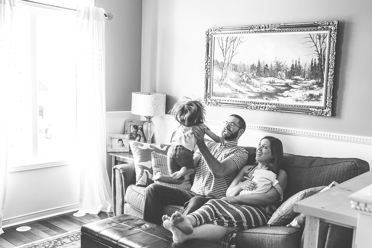 toddler boy jumping to parents on couch {Burlington Lifestyle Photographer}