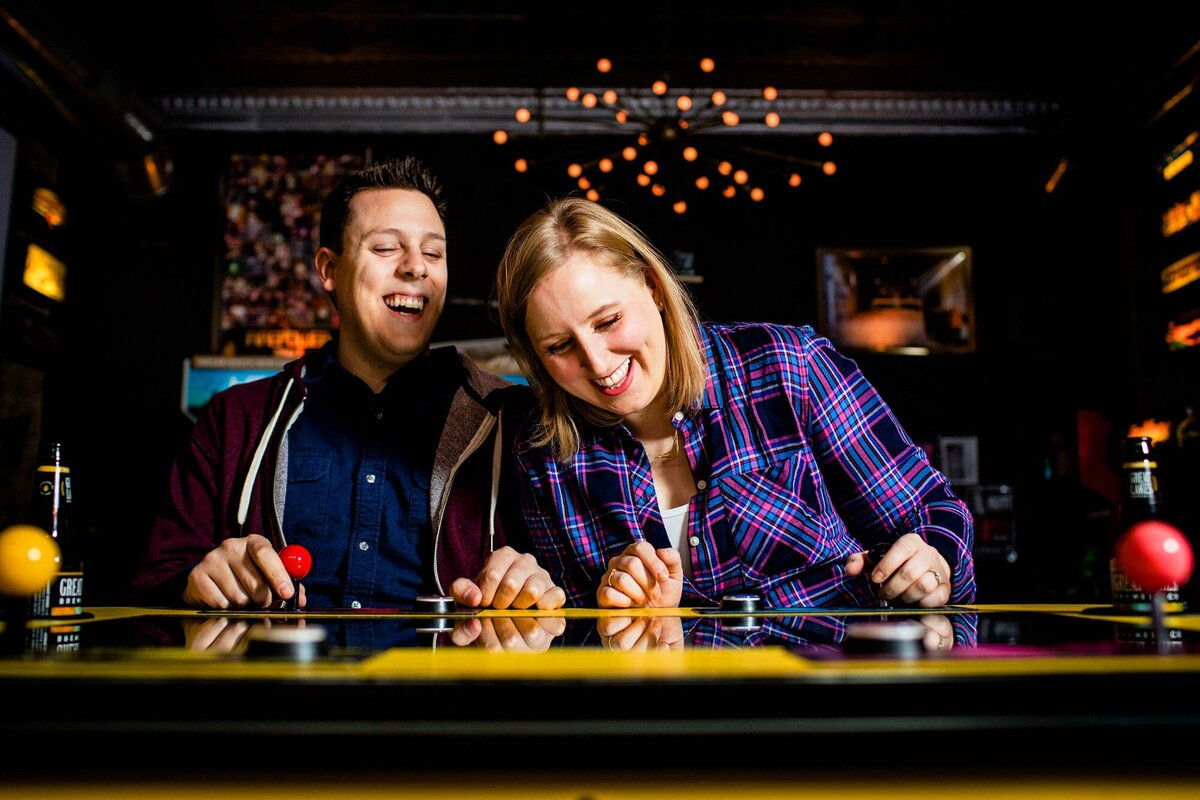 A couple laughs together during a Logan Arcade engagement session.