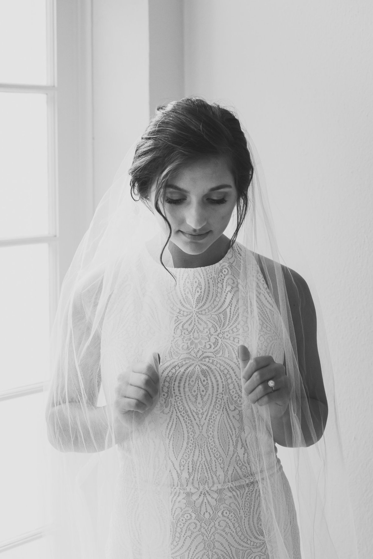 black and white of bride holding veil