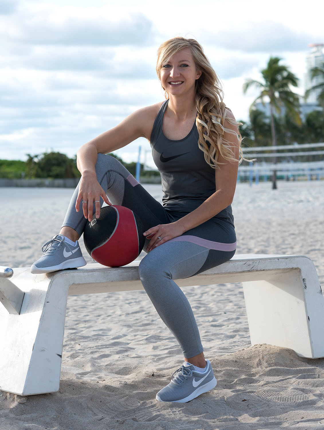 woman sitting on beach holding medicine ball