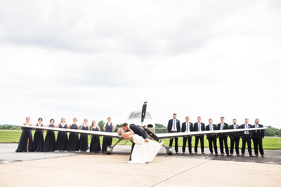A large bridal party poses by an airplane at the Helicopter Museum in West Chester PA