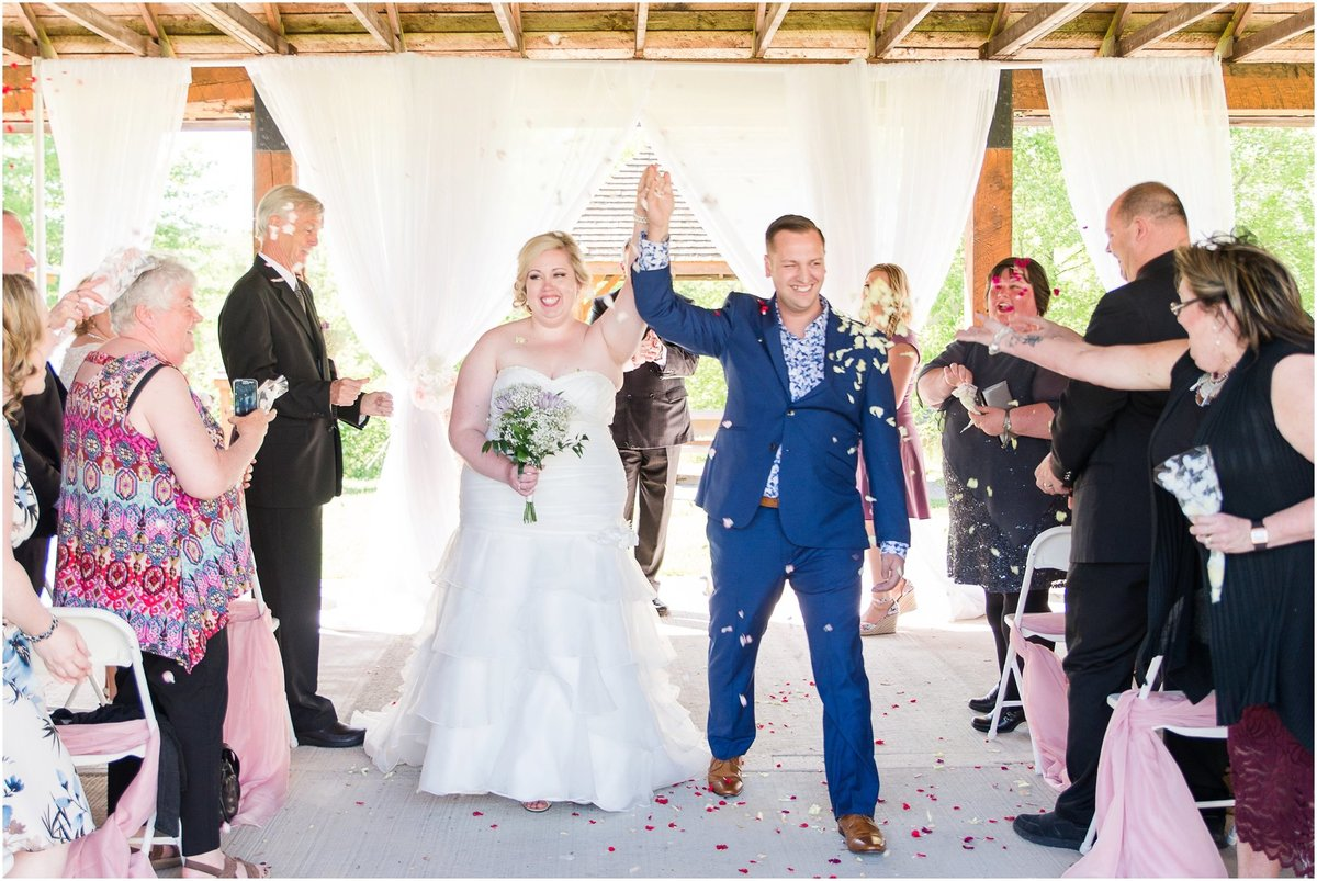 Guests throwing rose petals as bride and groom walk down the aisle