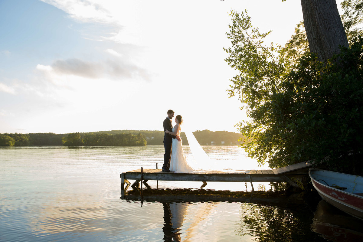 Bride and groom on dock at Lake Pearl Wrentham