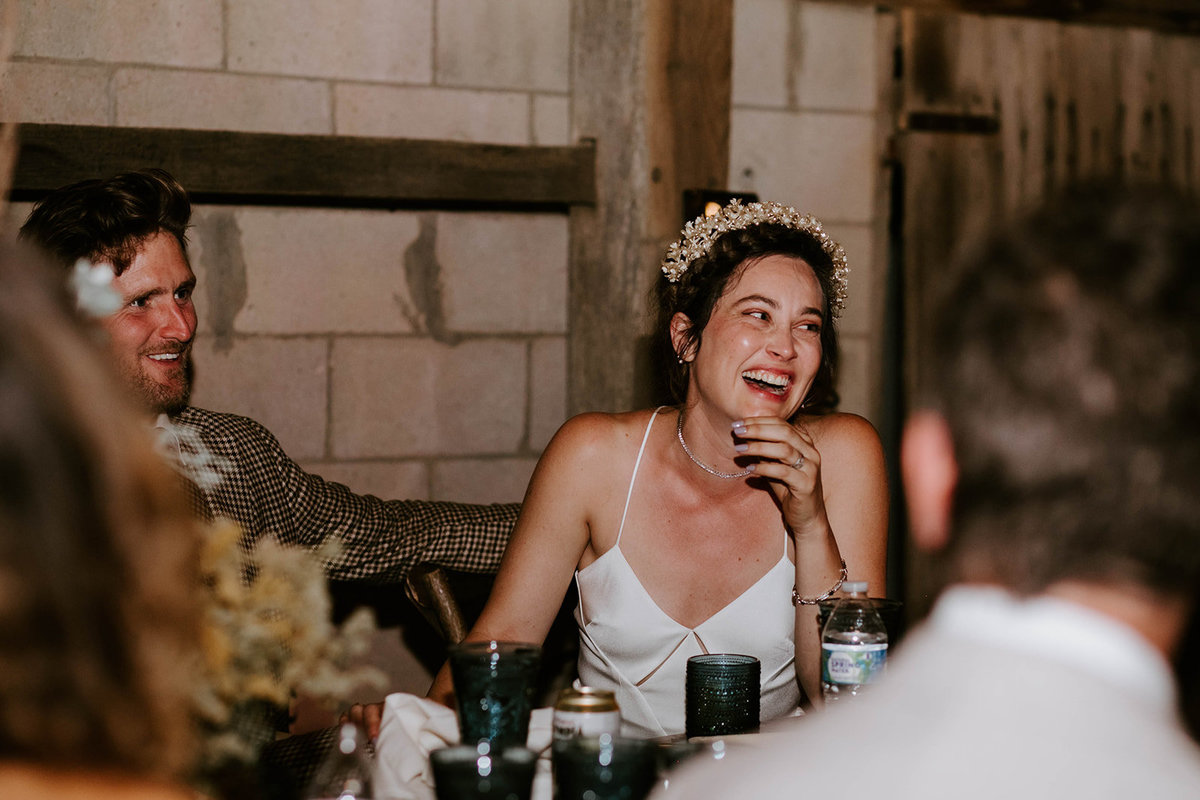 A bride laughs sitting at her wedding reception.