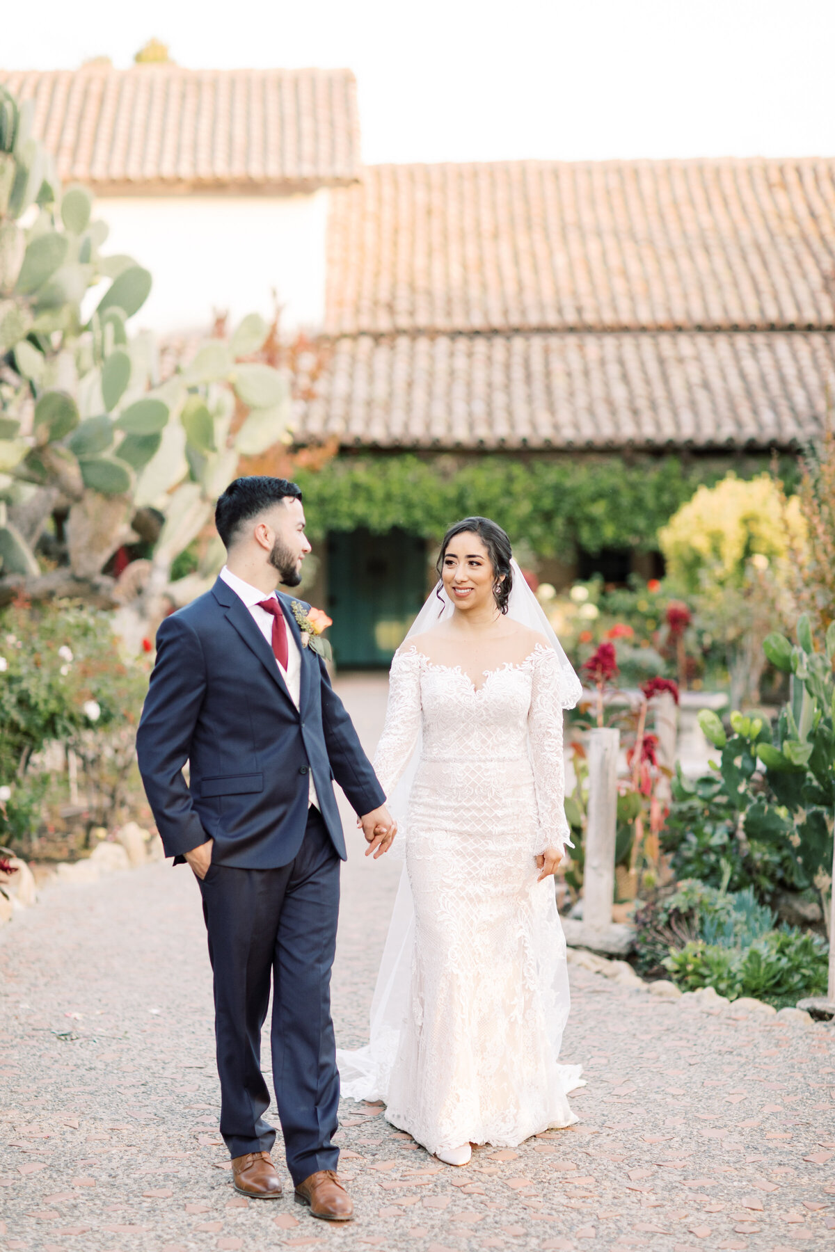 Bride and groom walk through a succulent garden in Carmel