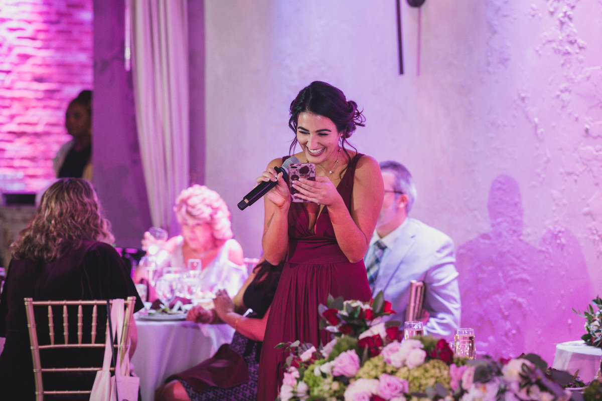 bridesmaid laughing while reading speech during wedding reception at The Loft by Bridgeview