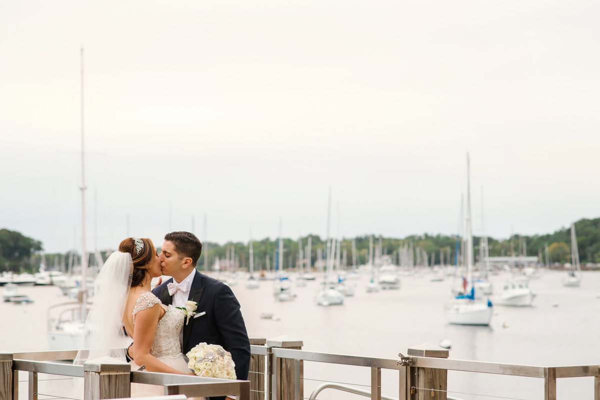 Bride and Groom kissing at the Dock of Harbor Club