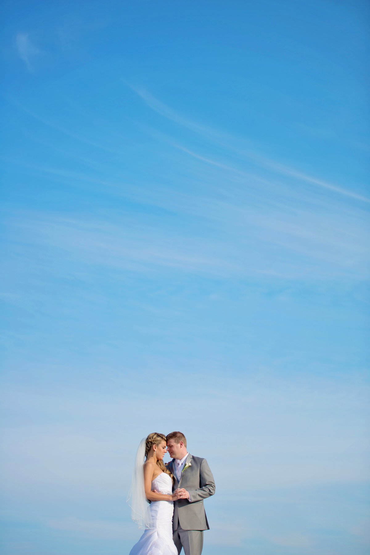Bride and groom photo with blue skies at Oceanbleu