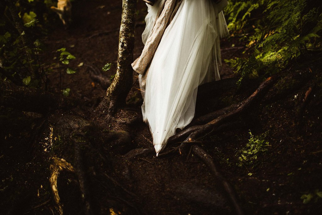 bride snags dress on branch while walking through forest at virgin creek falls