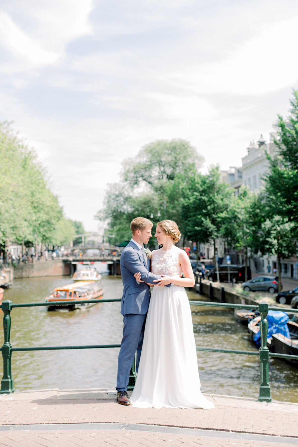 Wedding portrait of the bride and groom in Amsterdam overlooking the gracht for a photoshoot organized by Lovely & Planned
