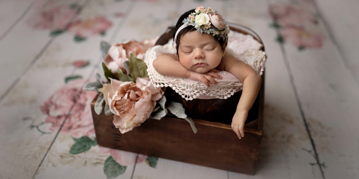 Newborn girl with flowers in a bucket