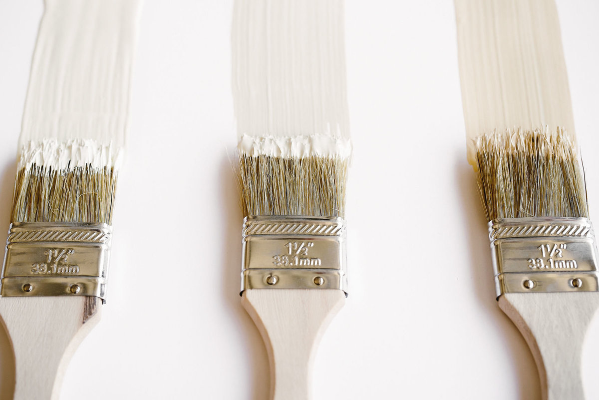 three wooden paint brushes with off white paint on bright white background