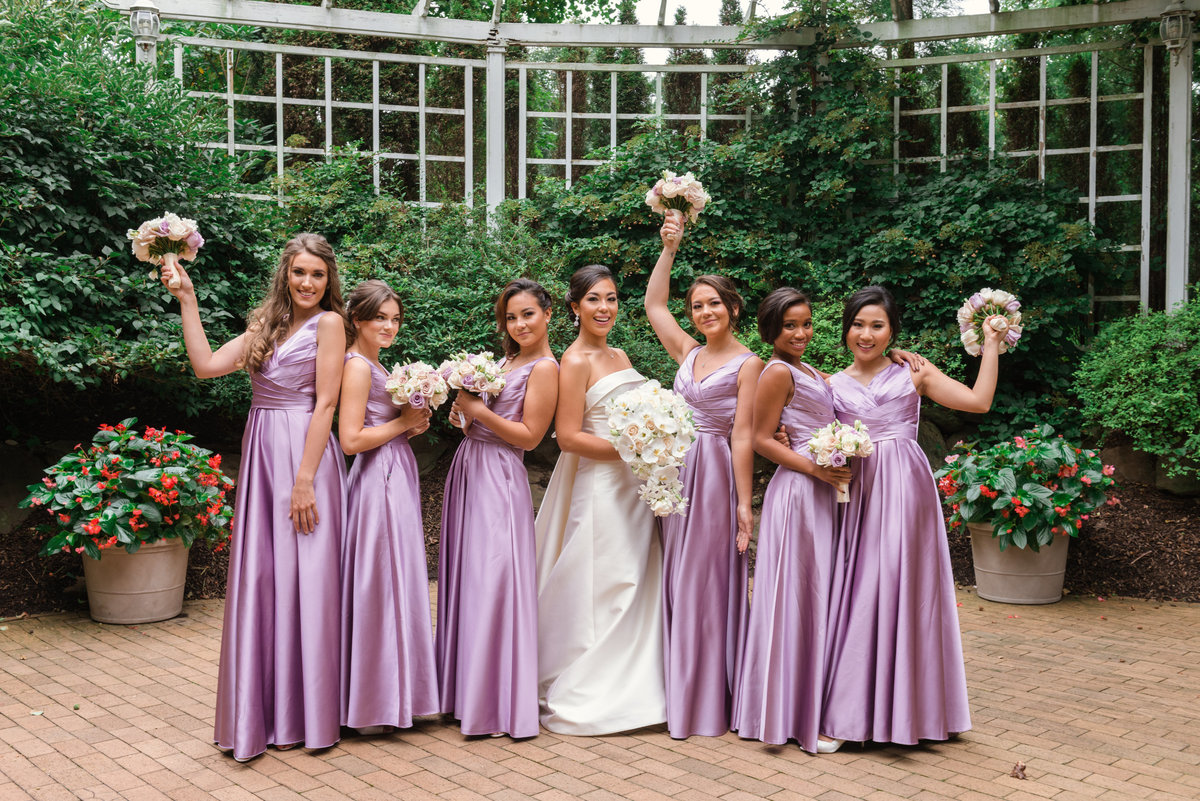 photo of bridesmaids with bride in the outdoor garden area from wedding reception at The Garden City Hotel