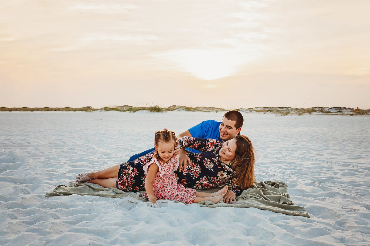 Family laying on beach, maternity