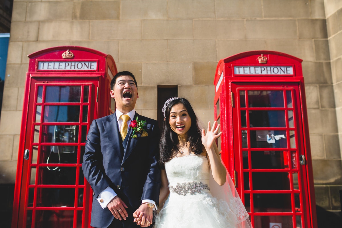 couple in front of red telephone boxes in manchester