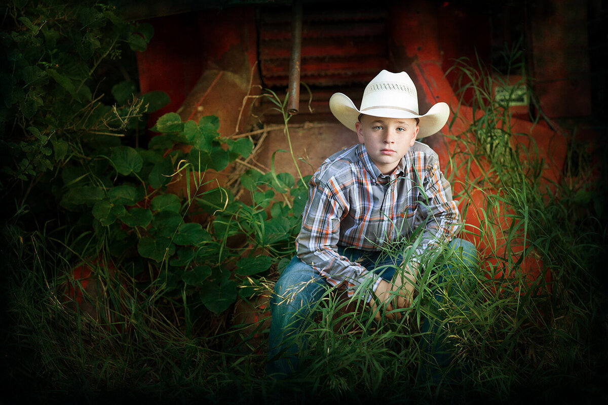 boy in cowboy hat, jeans and plaid shirt in billings montana, sitting on  old red farm machinery, cotton wood trees and green grass.