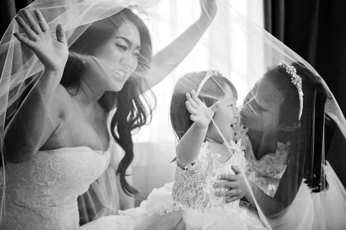 Bride under veil with her two daughter flower girls