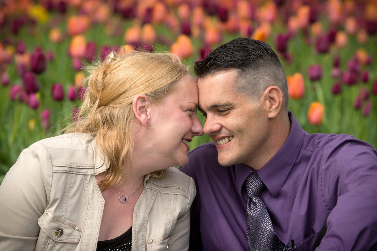 Couple give a smiling gaze in a field of purple and orange tulips