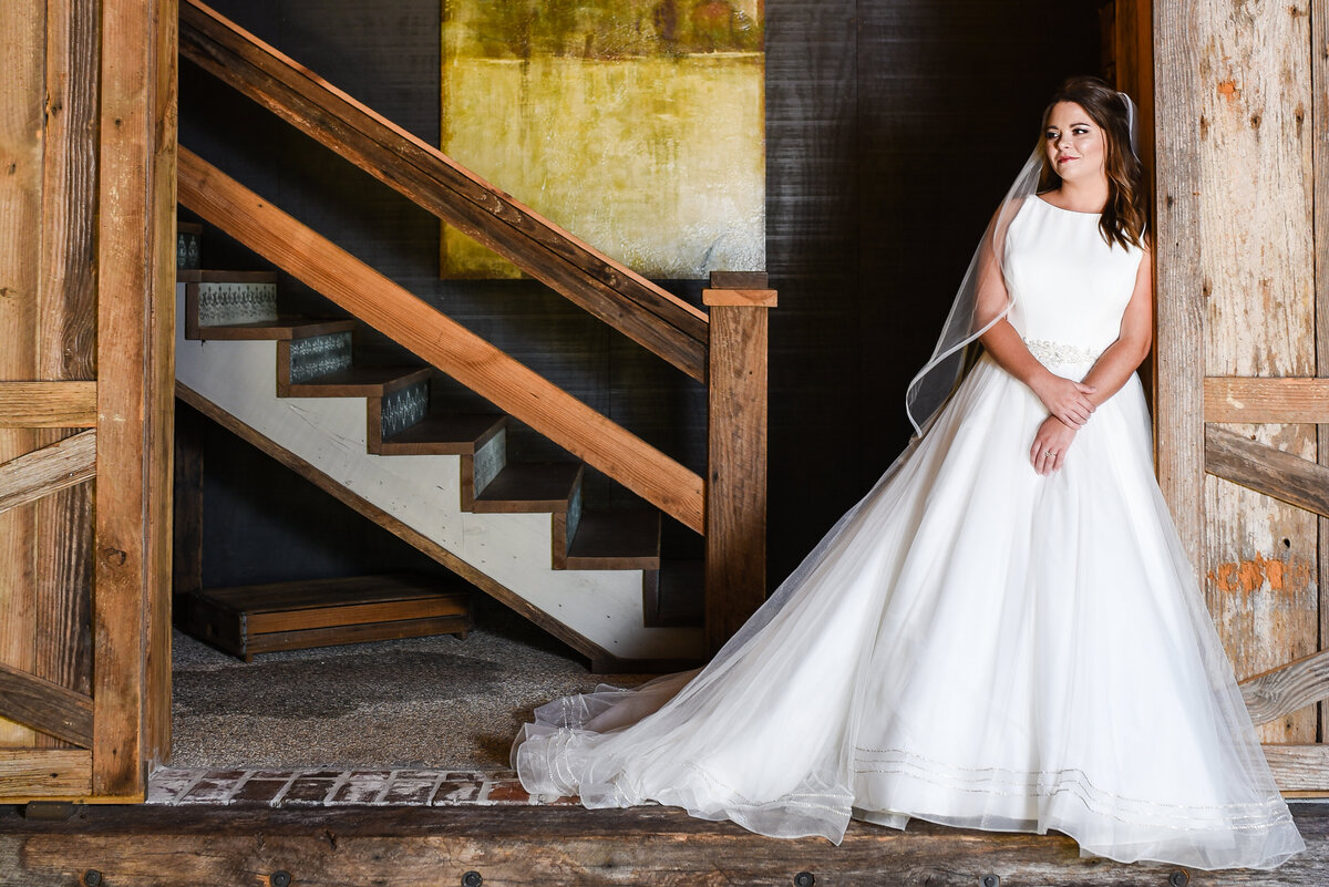 Beautiful bridal portrait photography: Bride leans in a dramatic doorway with chandelier behind at Greengates Farmhouse in MS