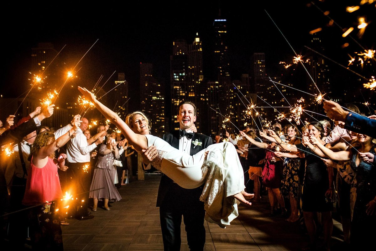A groom carries his bride as guests wave sparklers at a Savage Smyth wedding.