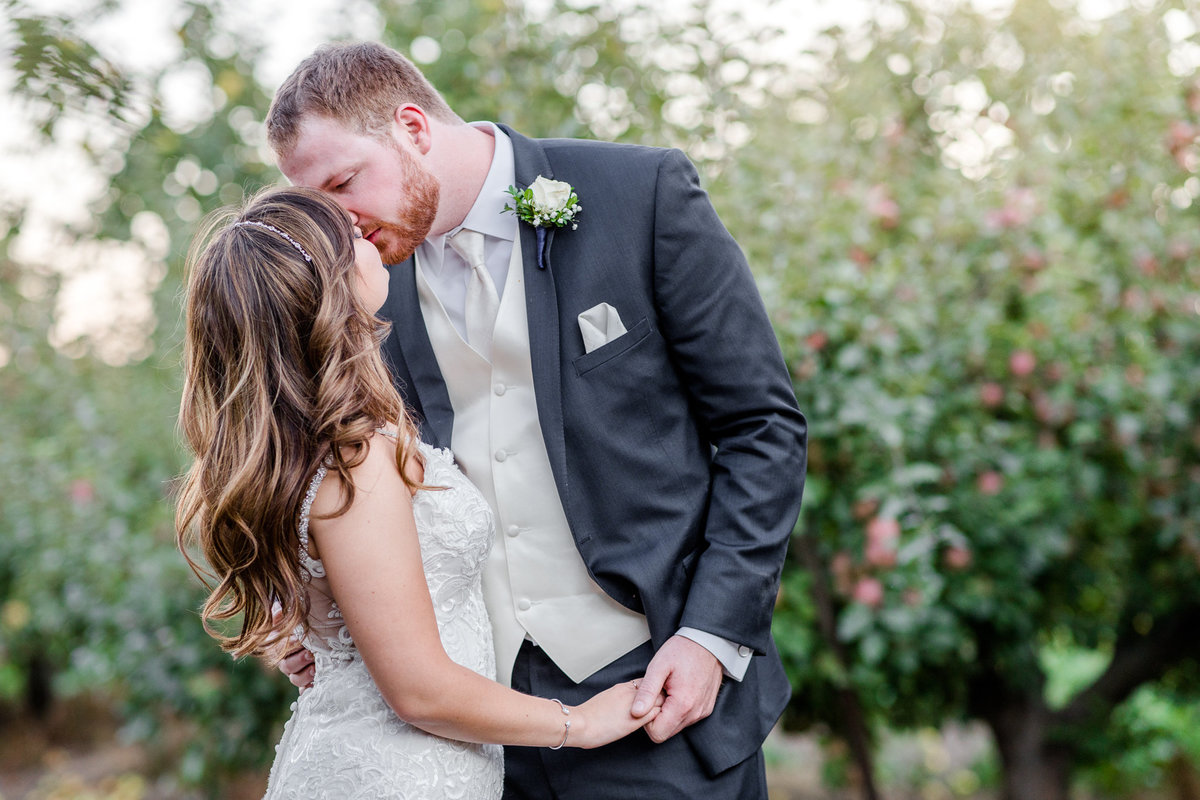 Bride and groom kiss in an apple orchard at their wedding south of the Bay Area