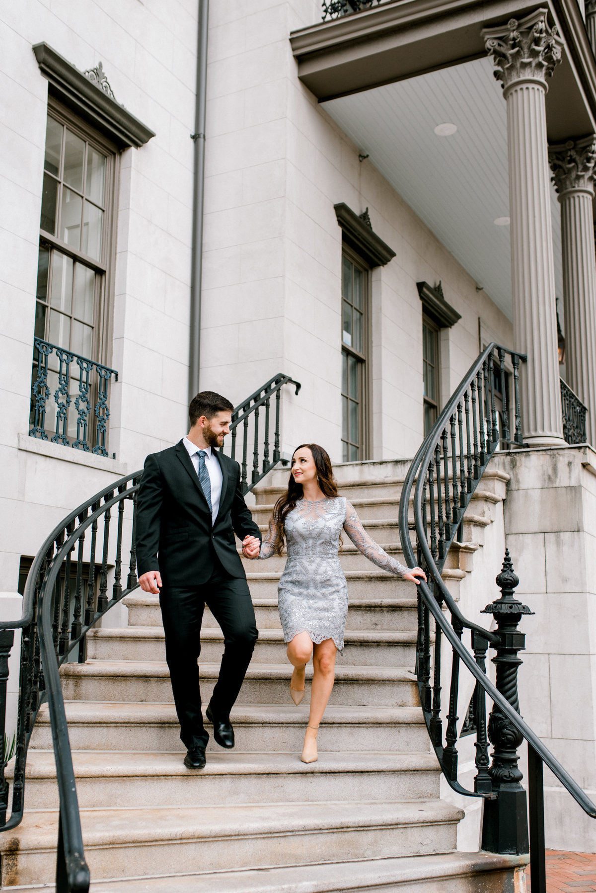 Couple walking down stairs during engagement session Savannah