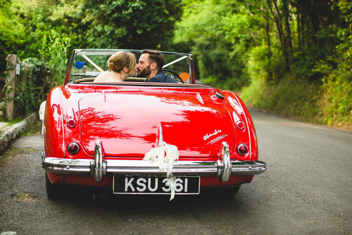 bride and groom kissing in a red austin healey convertible vintage  wedding car