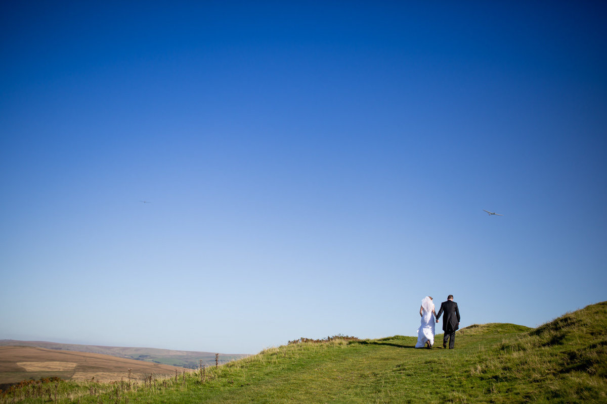 Bride and Groom walking on Dartmoor on their wedding day in Devon