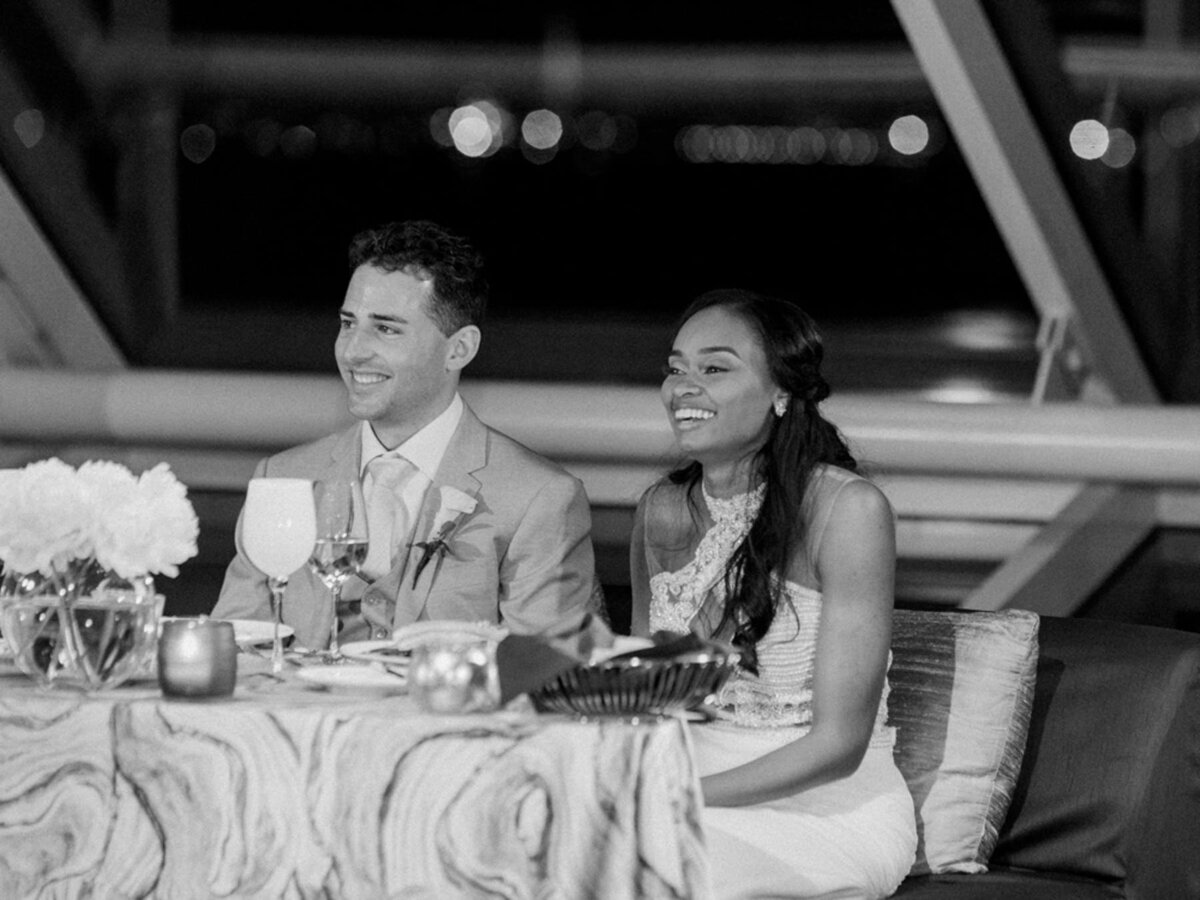 Black and white photo of bride and groom laughing during wedding reception