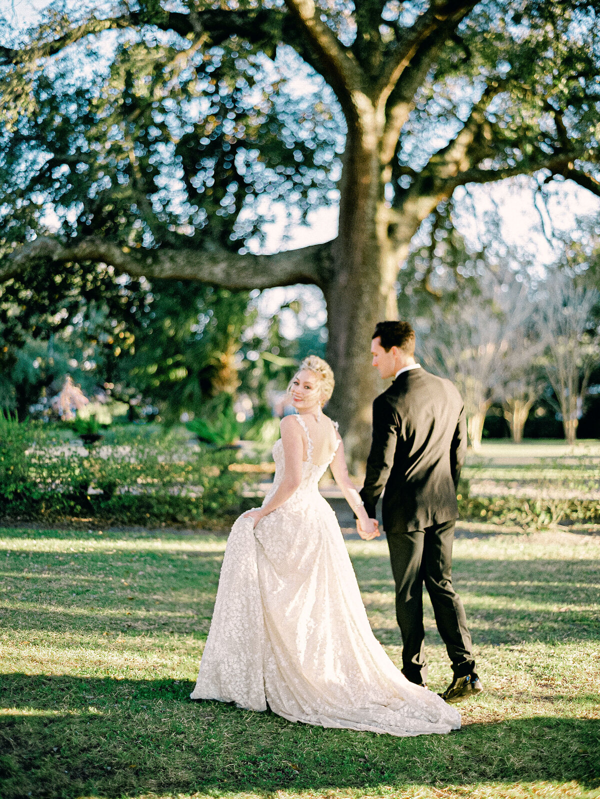 bride in white wedding dress walking with groom in black tuxedo in green garden Charleston
