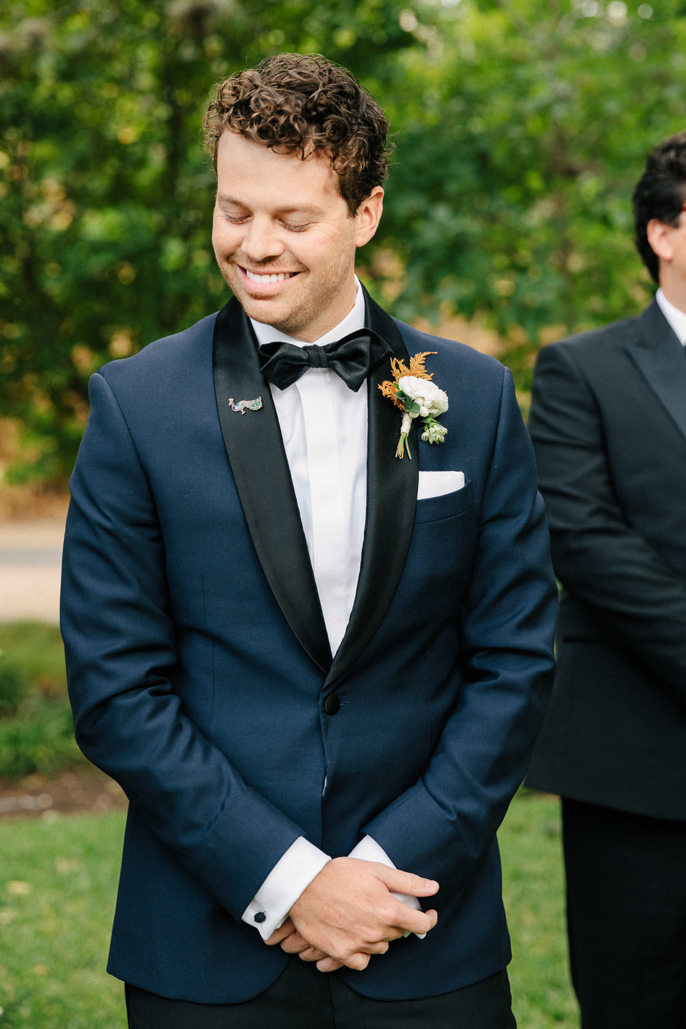 Groom smiling in navy blue tuxedo