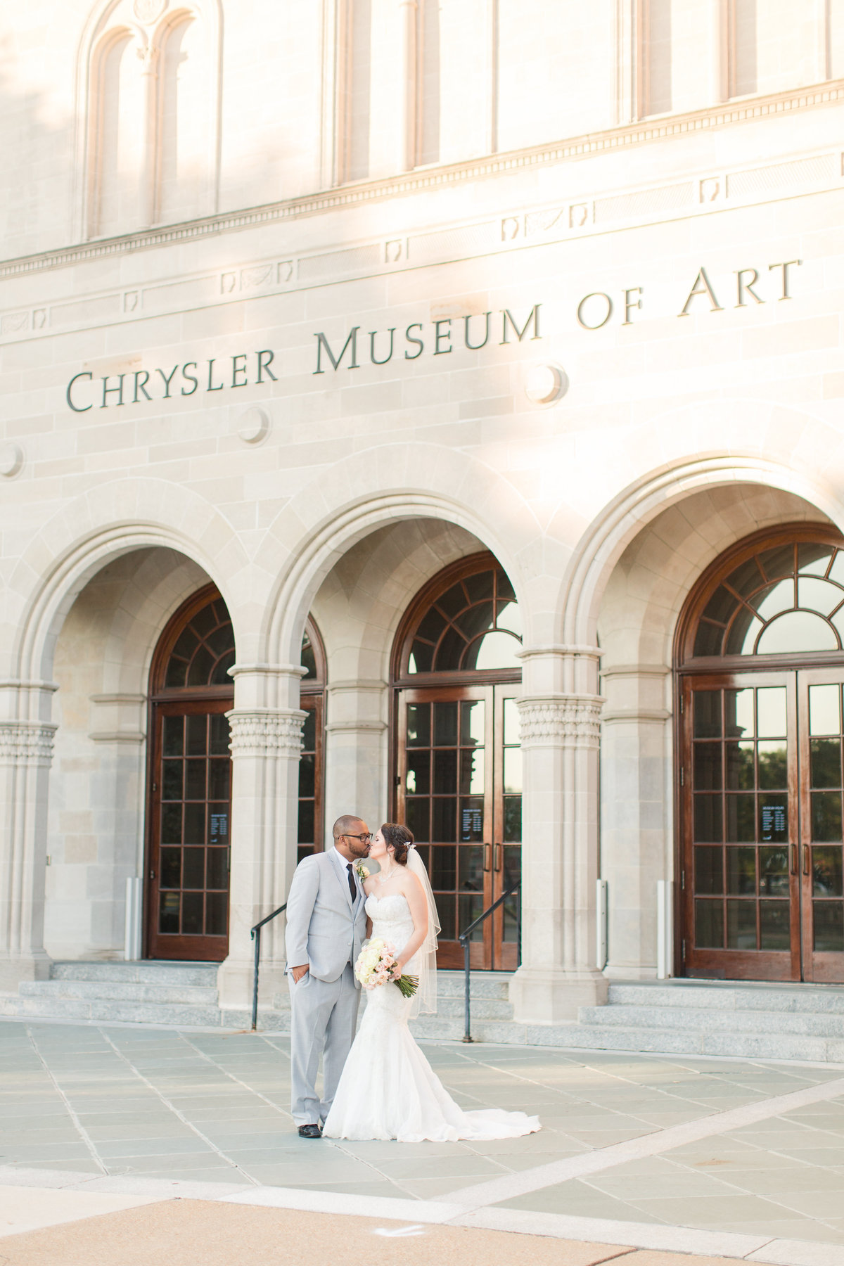 bride and groom kissing in front of Chrysler Museum of Art