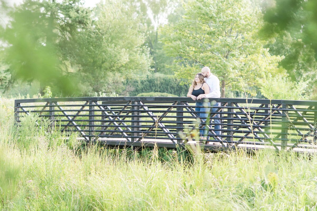 Couple embracing on a park bridge