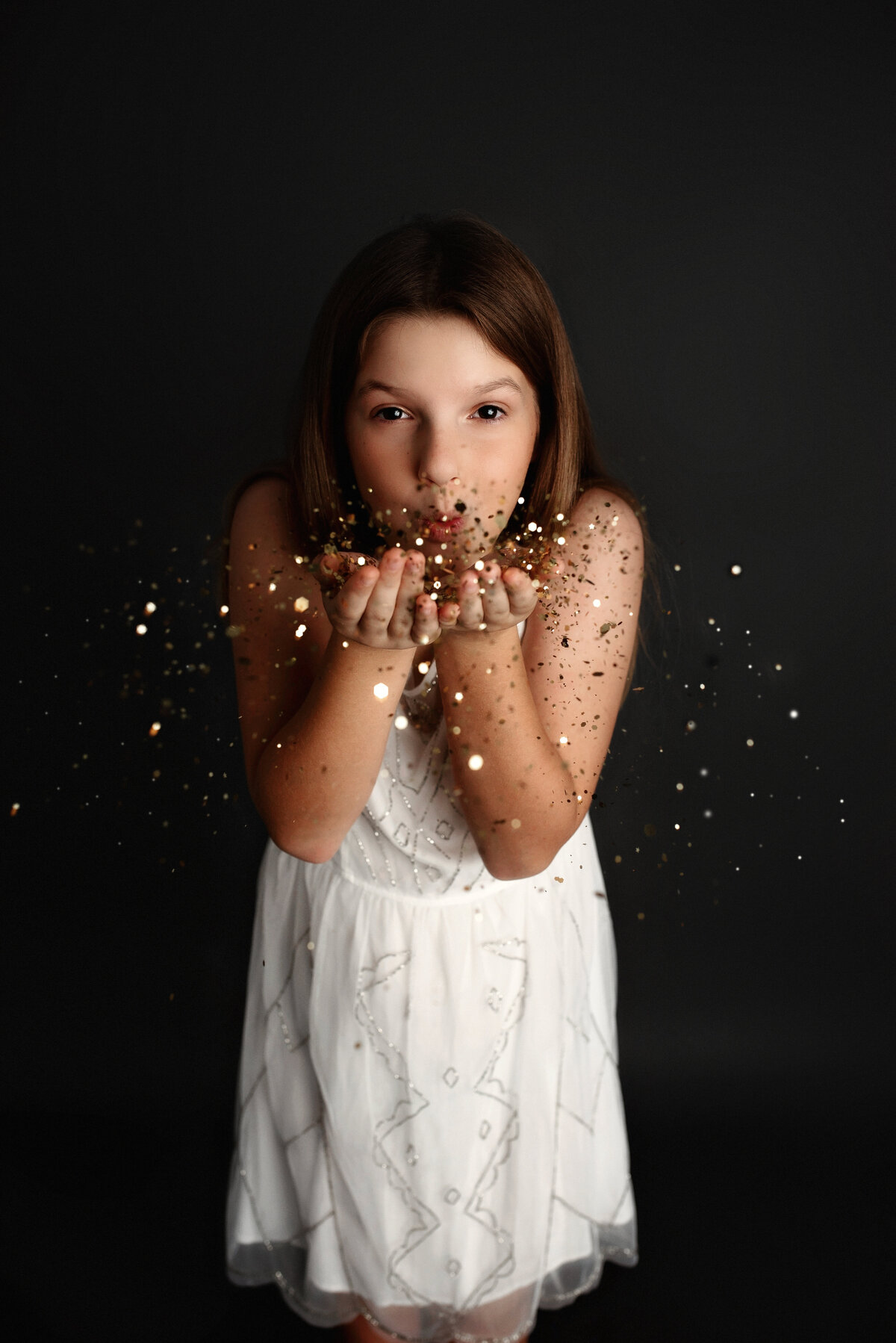 young girl blowing glitter