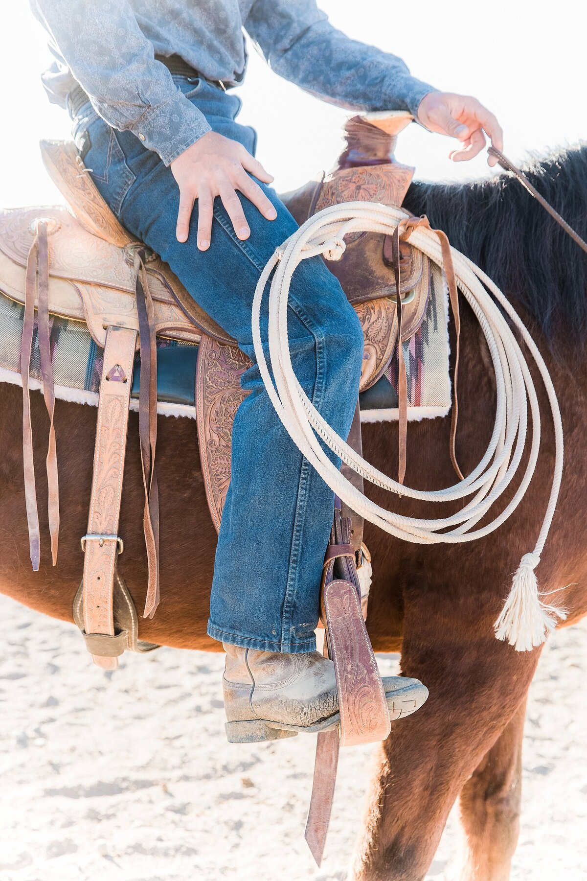 close up of a cowboy sitting in a western saddle with a rope attached.