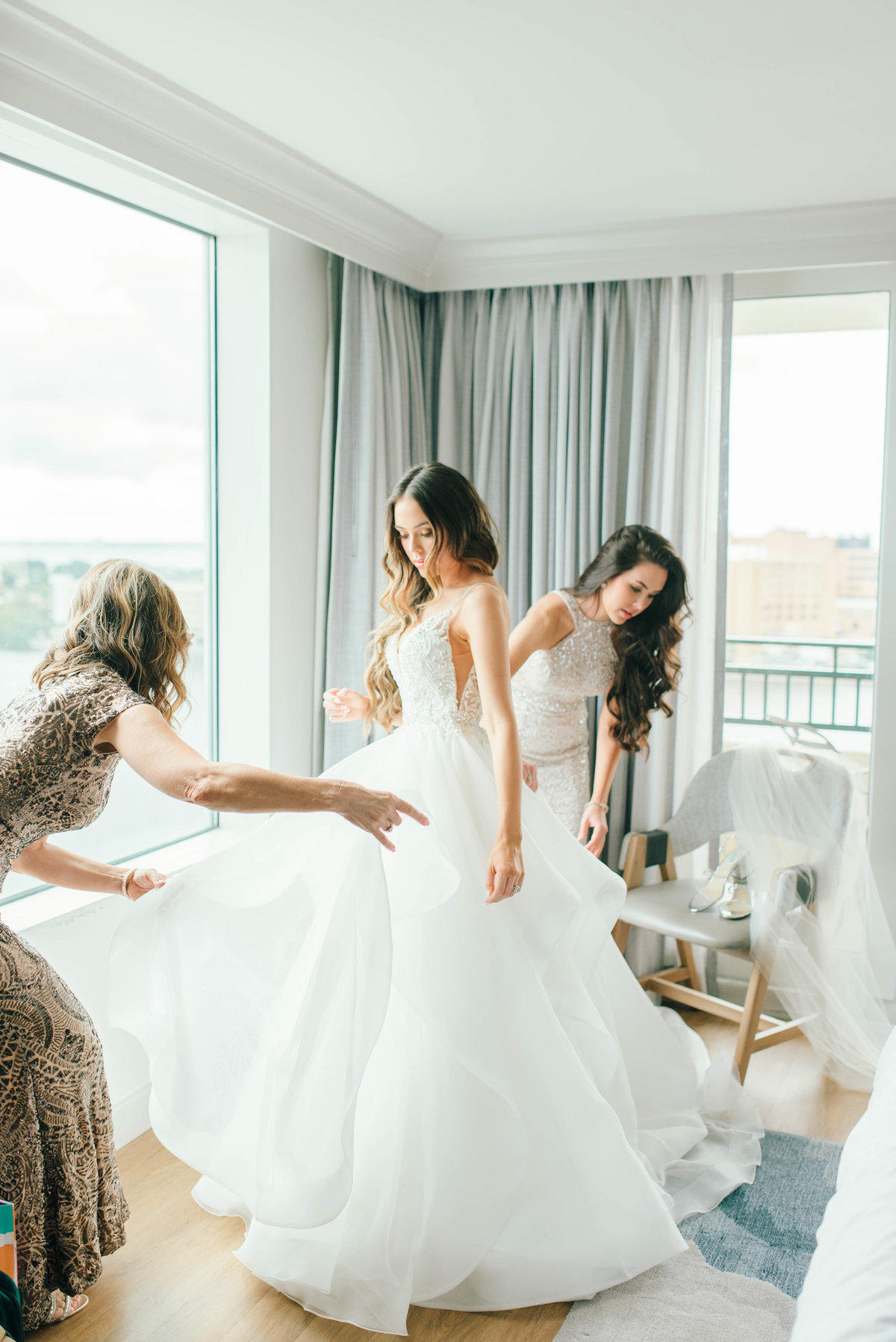 Mother of the bride and sister of the bride helping with brides wedding dress