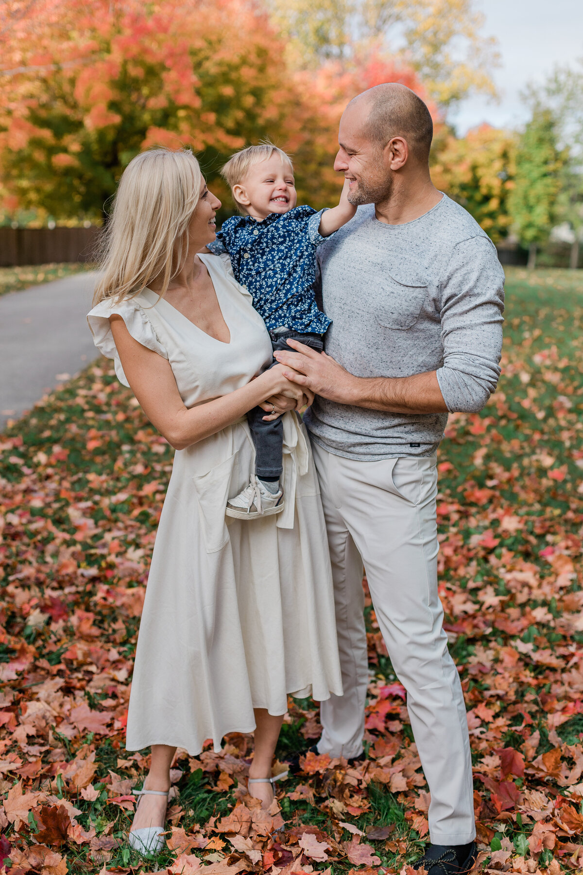 father, mother and son in family photo with fall leaves