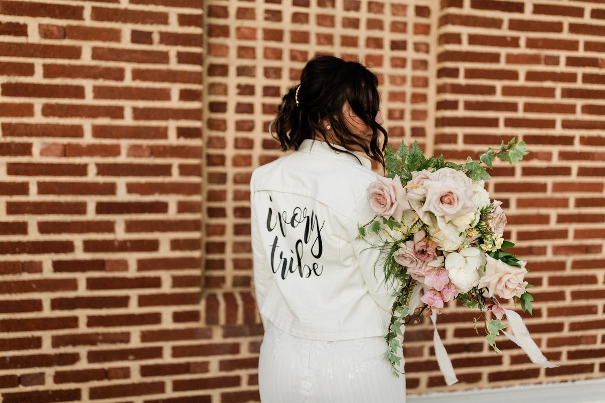 bride in a leather jacket holding her bouquet in front of a brick wall
