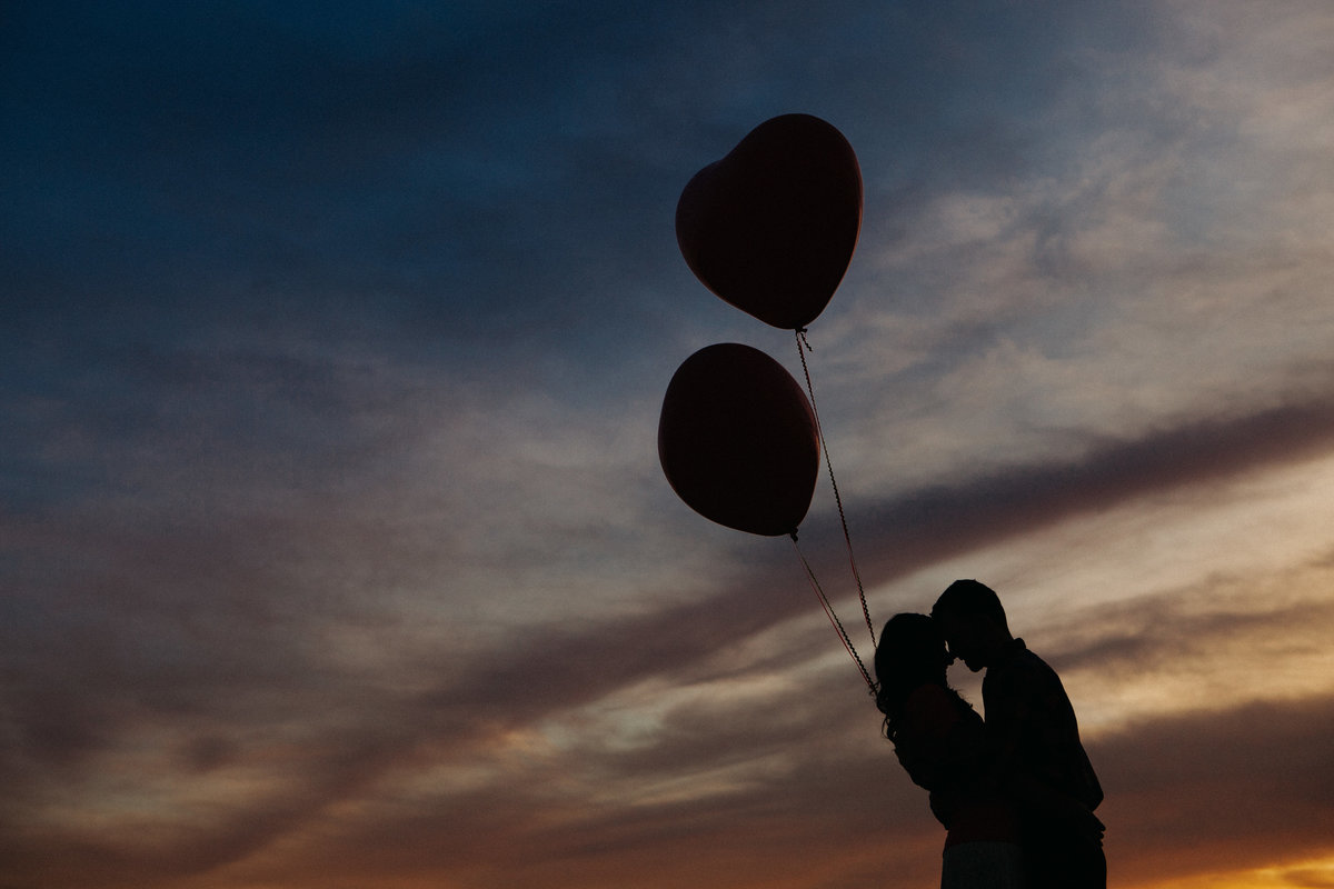 silhouette with balloons engagement photo