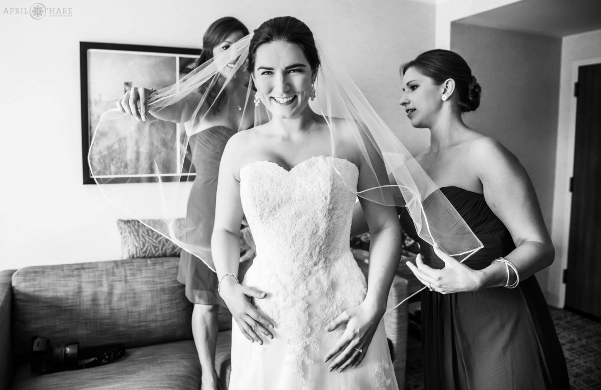 A B&W Colorado Wedding Photo of a bride getting help with her veil