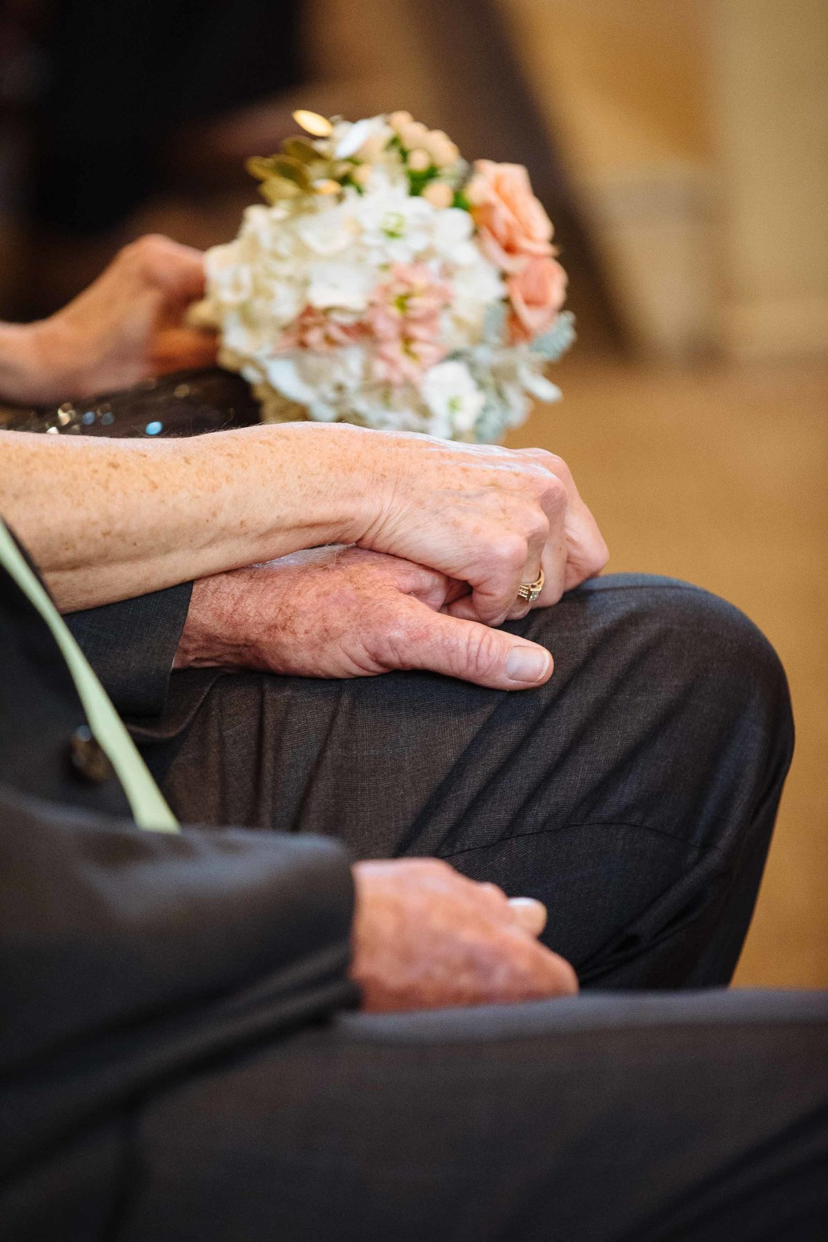 An elderly couple hold hands in a church at a wedding ceremony.